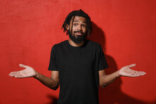 Confused Puzzled Young African American Man Guy With Dreadlocks 20s Wearing Casual Black T-shirt Posing Spreading Hands Looking Camera Isolated On Bright Red Color Wall Background Studio Portrait.