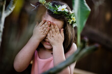 Young Girl With Flower Crown Covering Eyes