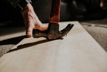 Close Up Of Person Removing Nail From Board With Hammer