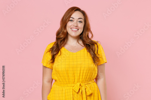Stampa su Tela Smiling beautiful attractive young redhead plus size body positive female woman girl 20s in yellow casual dress posing looking camera isolated on pastel pink color wall background studio portrait