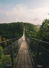 Brown Wooden Hanging Bridge In The Evergreen Tropical Forest Over Top