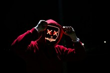 A Man Wearing A Red Hoodie Wit...