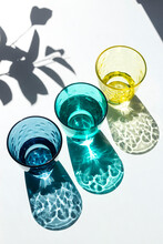 Coloured Glass Cups Filled With Water Under The Strong Sunlight