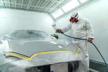 Automobile Painting. Car Painter With Gun In Chamber. Spray Operation.