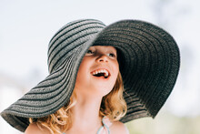 Portrait Of A Young Girl Smiling Outside With A Large Sun Hat On