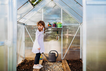 Young Girl Standing On Plant Bed In Greenhouse In Spring