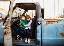Young Brother And Sister Sitting And Hugging In Vintage Truck