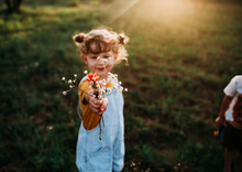 Young Girl Holding Bouquet Of Wild Flowers Outside In Golden Hour