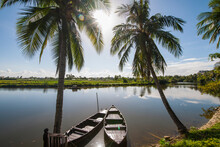 Two Rowing Boats Parked At Calm River Close To Hoi An