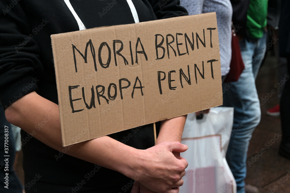 Fototapeta Demonstrator holds a cardboard with German text Moria brennt, Europa pennt (Moria is burning, Europe is sleeping), demonstration in Lubeck for accommodation of refugees after fire in the Greek camp