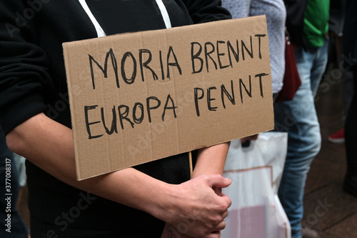 Demonstrator holds a cardboard with German text Moria brennt, Europa pennt (Mori Wallpaper Mural