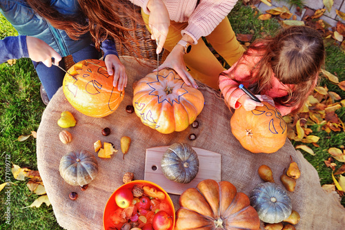 Photographie Top view of family carving pumpkins