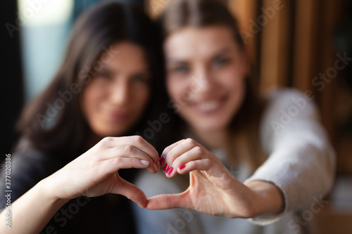Two lovely girls smiling in a cafe and making a hearth shape with their hands Canvas Print