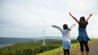 Asian child girl and mother raised their hands to fly and playing in the wind turbine field with fun together