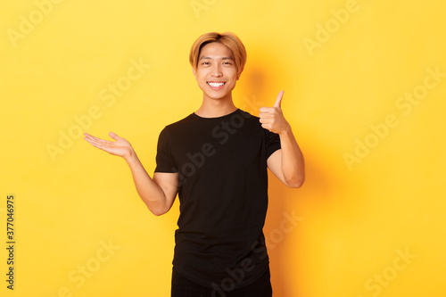 Obraz Satisfied and happy attractive korean guy smiling, showing thumbs-up in approval with rejoice, holding something on hand, standing yellow background - fototapety do salonu