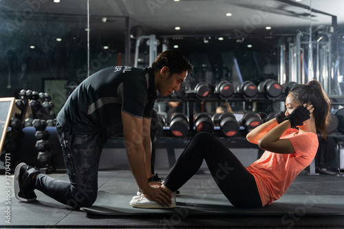 Personal trainer to practice sit-ups in the gym Fotobehang