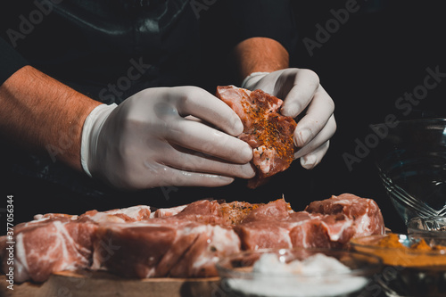 Obraz A man in gloves prepares and marinates pork with spices for cooking kebabs, uses salt, curry and basil. - fototapety do salonu