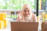 Fototapeta Sypialnia - Muslim woman video calling to her friend during virus pandemic.