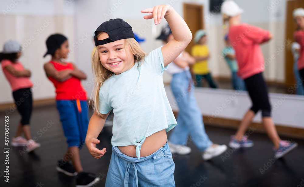 Fototapeta Portrait of emotional girl doing hip hop movements during group class in dance studio