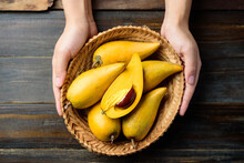 Eggfruit Or Canistel In A Basket Holding By Hand On Wooden Table, Thai Fruit, In Thai Names Such As Xiantao, Lamut Khamen Or Mon Khai