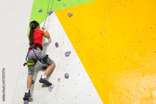 Obraz Sporty little girl climbing artificial boulder on practical wall in gym - fototapety do salonu