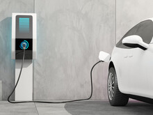 Futuristic Electric Car Connected To The Charging Station To Charge The Battery Against The Background Of A Concrete Wall. 3d Render.