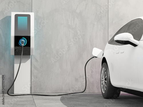 Fotografie, Tablou Futuristic electric car connected to the charging station to charge the battery against the background of a concrete wall