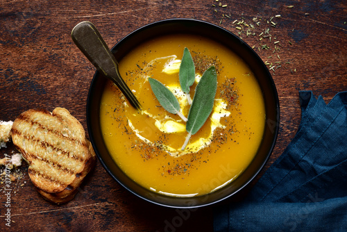 Fototapeta Delicious pumpkin soup with vegan cream and sage. Top view with copy space. obraz