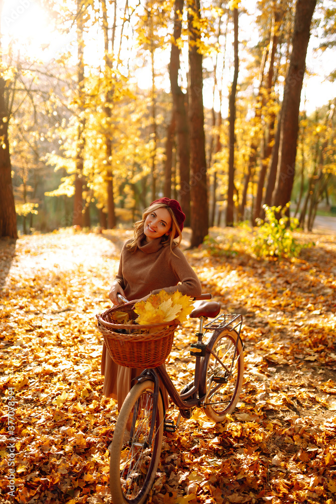 Fototapeta Autumn woman in autumn park. Happy young woman posing with bike in autumn forest. - obraz na płótnie