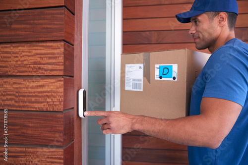 Fotografia, Obraz Male Courier Delivering Package To House Ringing Front Doorbell