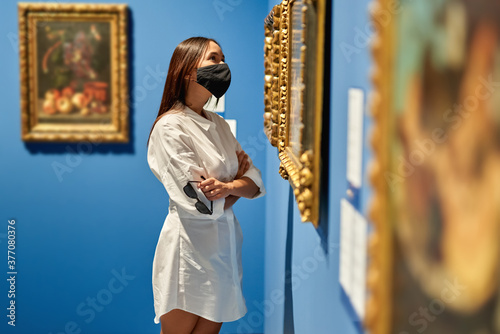 Fotografia Woman visitor wearing an antivirus mask in the historical museum looking at pictures