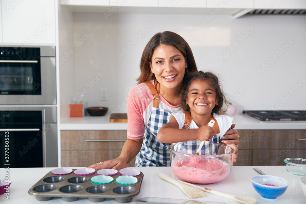 Fototapeta Portrait Of Hispanic Mother And Daughter Having Fun In Kitchen At Making Cake Together