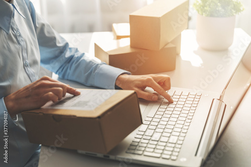 person preparing online store orders for shipping using laptop - 377094187