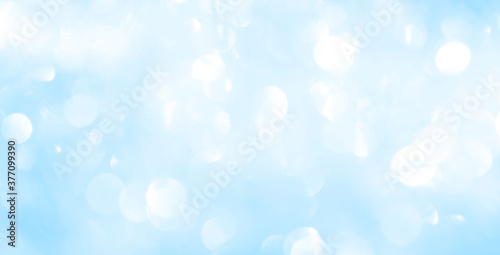 Obraz Bokeh light on blue background, sky with circle glitter light blue. Snow abstract soft glowing with vivid bright light and bokeh blur effect.  - fototapety do salonu
