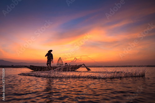 Asian fisherman on wooden boat throwing a net for catching freshwater fish in na Canvas