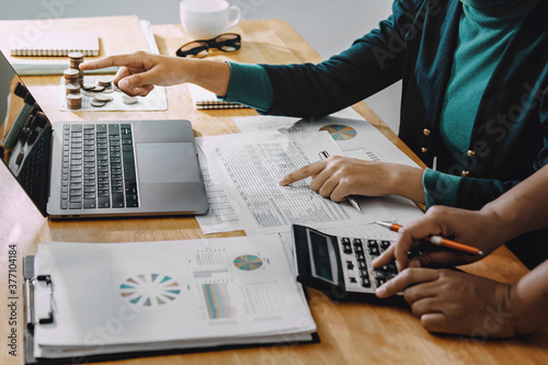 businessman working in office with using a calculator to calculate the numbers finance accounting concept - 377104184