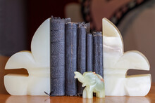 Old Books (bibles And Prayer Books) Between Onyx Bookends With An Elephant.