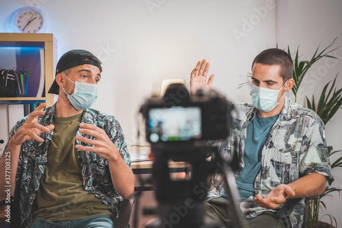 Photo Influencers with face mask making an interview with video camera