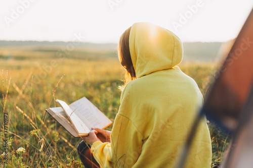 Young woman traveler in yellow hoodie reading book against the tent Fototapete