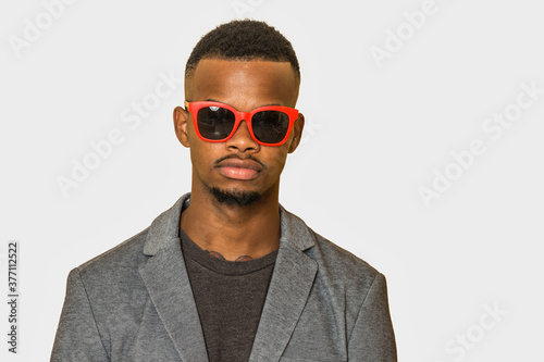 Fototapeta Serious black man in sunglasses looking at camera