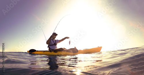 Photographie Fisherman standing on a kayak catch a fish against sunset.