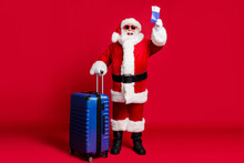 Full Length Photo Of Retired Old Man White Beard Hold Suitcase Tickets Prepare Flight Abroad Wear X-mas Santa Costume Glove Coat Belt Sunglass Cap Boot Isolated Red Color Background