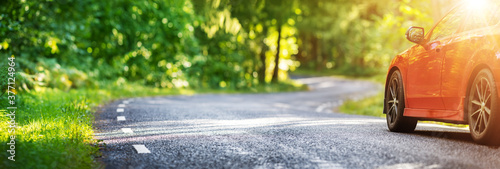 Obraz red car on asphalt road in summer - fototapety do salonu