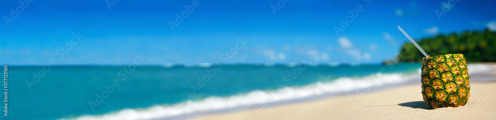 Fototapeta Pineapple cocktail on sand on caribbean beach. Travel summer vacation. Tropical destinations