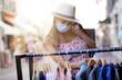 Leinwandbild Motiv Young woman doing shopping in tourist area, wearing face mask