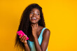 Photo portrait of african american woman with long wavy hair holding pink smartphone in two hands laughing wearing blue singlet isolated on vivid yellow colored background