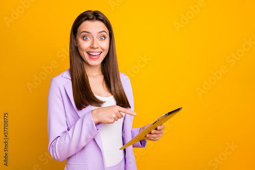 Fototapeta Photo of crazy business lady holding e-reader read good news directing finger screen showing amazing discount price wear lilac suit isolated yellow color background obraz