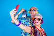 canvas print picture - Couple of senior man and woman on blue background taking selfie - Grandpa and grandma live streaming isolated with stereo