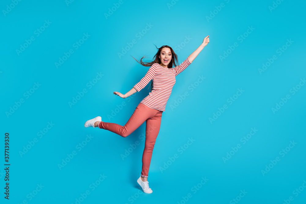 Fototapeta Full length photo of excited energetic girl hold hand try catch dream parasol her hairstyle wind air blow wear good look casual outfit sneakers isolated over blue color background