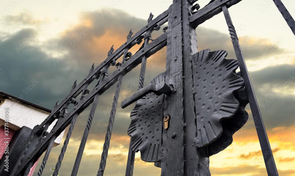 Fototapeta wrought iron fence gate against sky